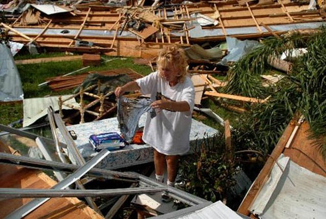 Linda Molitor pulls wet and soiled clothing from the rubble of her destroyed mobile home in Punta Gorda FL